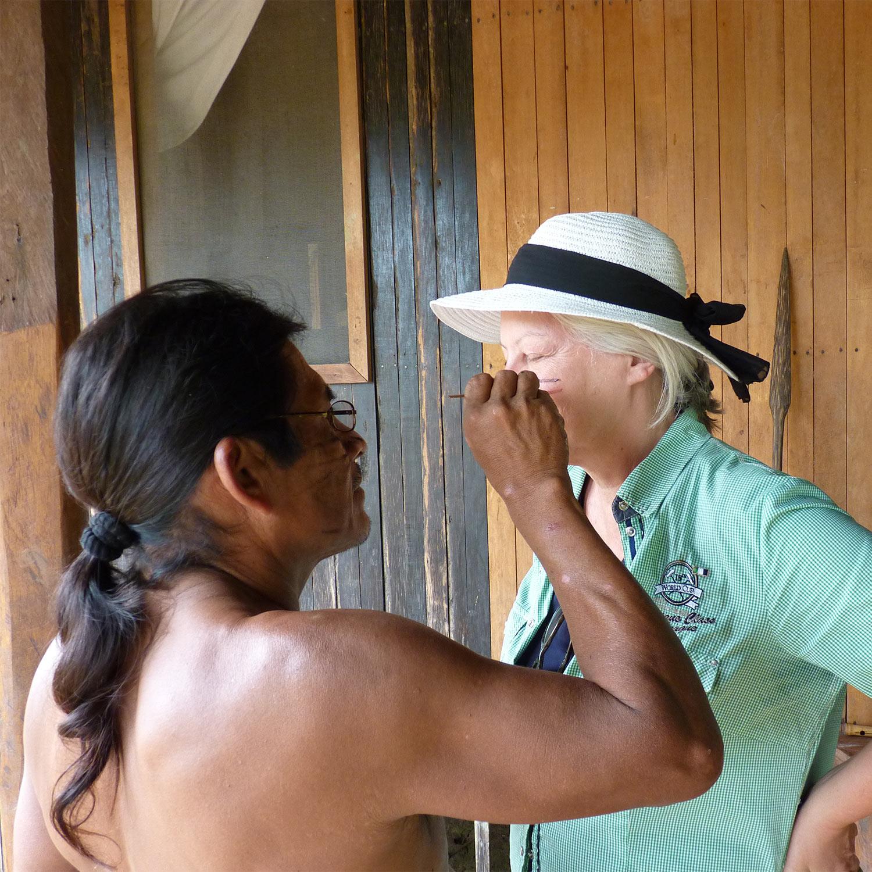 Ureinwohner in Ecuador bemalt Gründerin Margot Esser im Gesicht