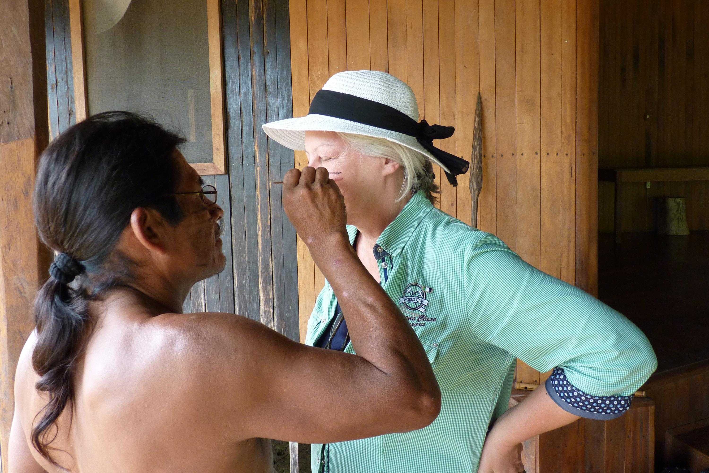 Margot Esser wird von einem Ureinwohner bemalt