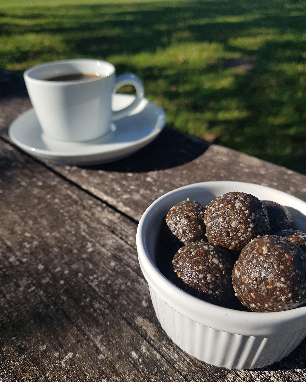 Schwarze Sesamkraft Powerkugeln in Porzellan-Schüssel und einer Tasse Kaffe im Hintergrund