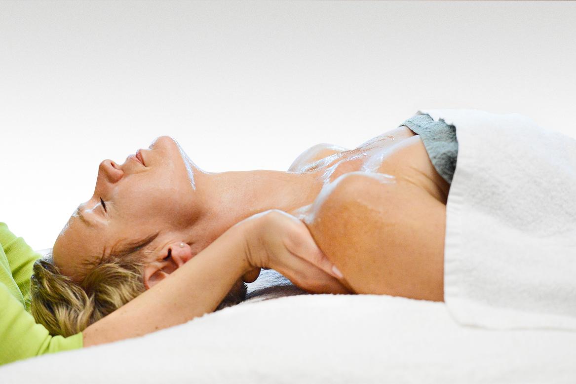Frau liegt während einer Behandlung entspannt auf dem Rücken und wird an den Schultern leicht angehoben