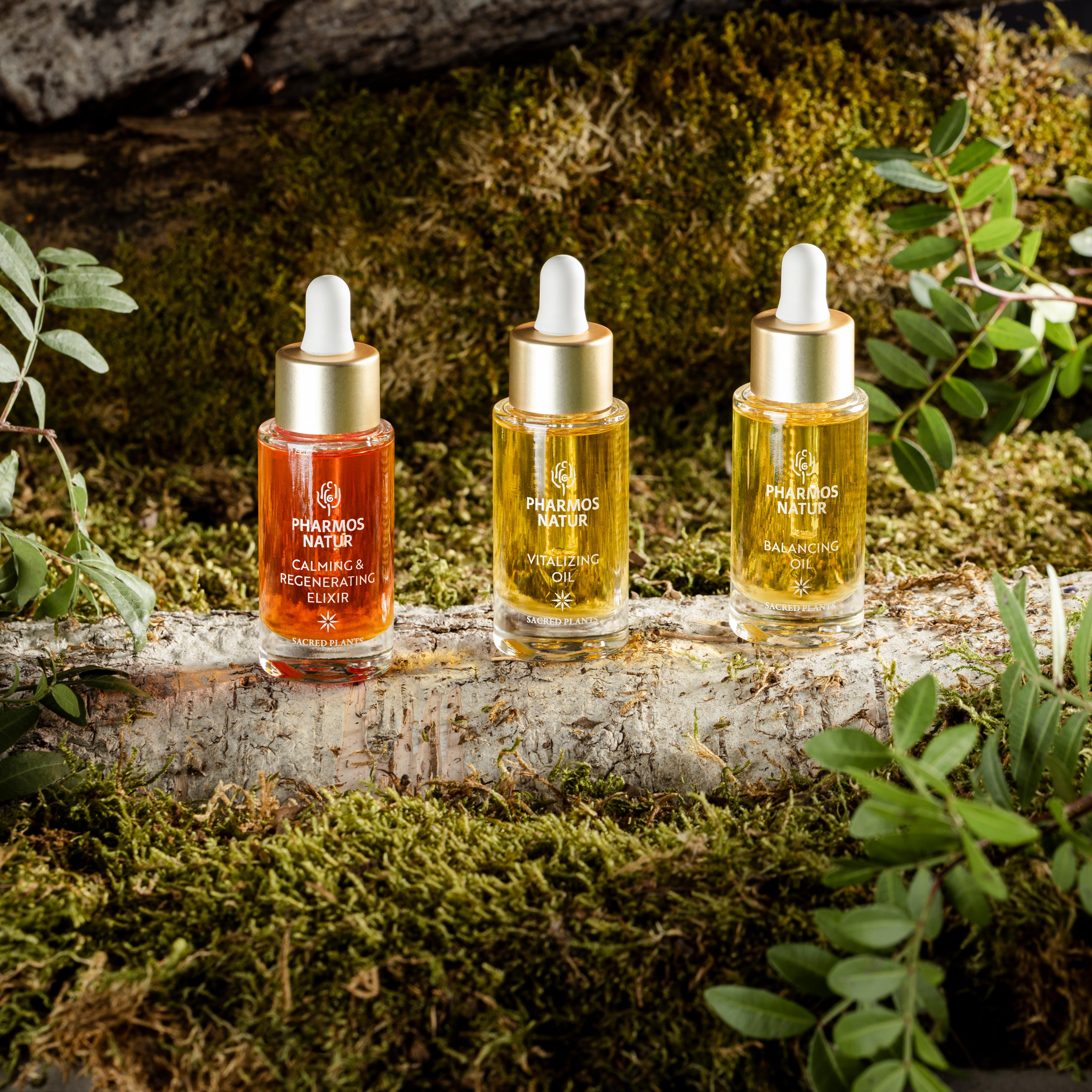Drei Oil Seren auf einem Holzstamm mit Moos und Blättern