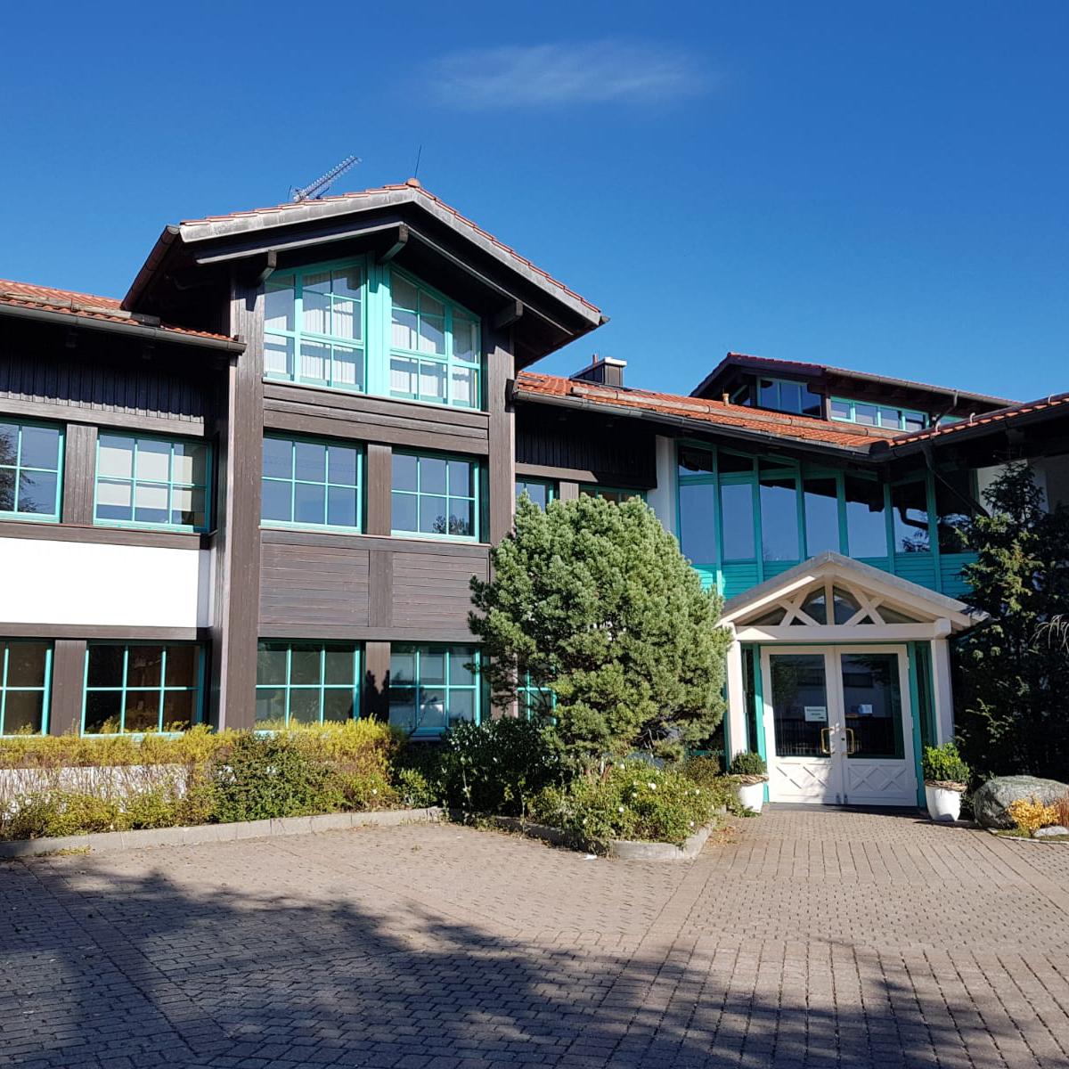 Das Pharmos Natur Firmengebäude in Bernried mit braun grünen Farben und blauem Himmel