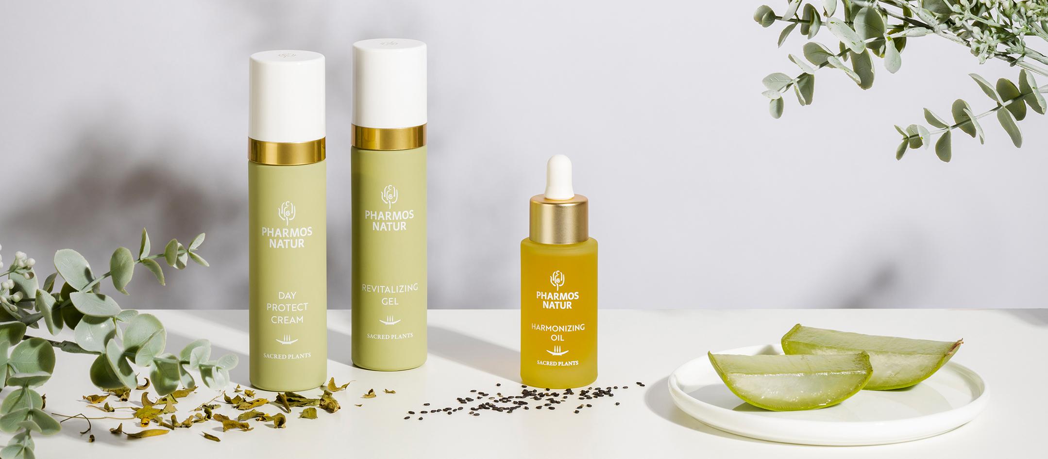 Produktabbild: Hellgrüne Day Protect Cream und Revitalizing Gel Flaschen neben gelbem Harmonizing Oil